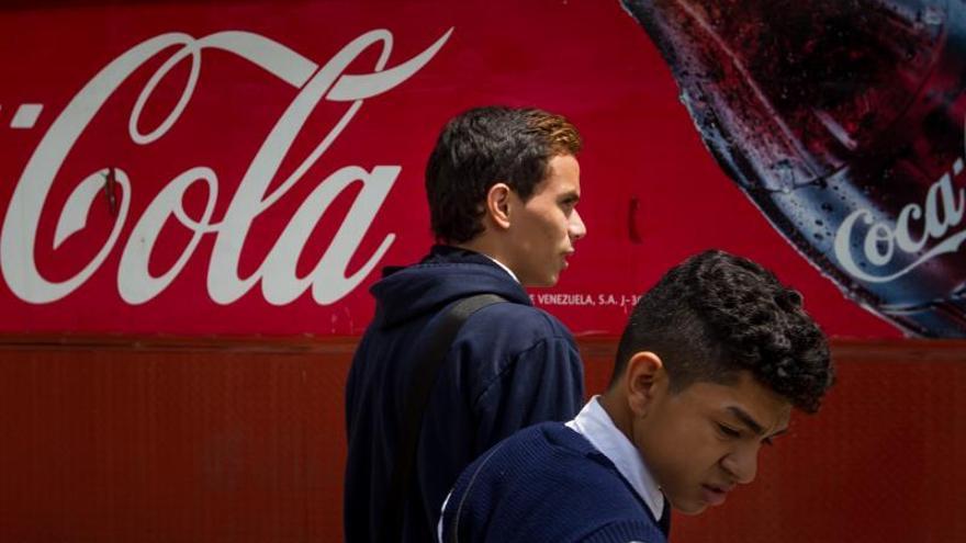 Dos hombres caminan junto a un kiosco de Coca-Cola.
