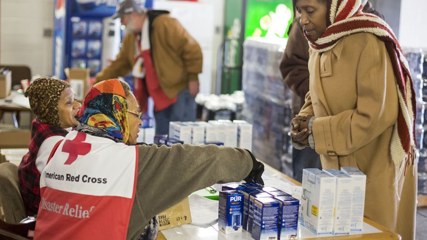 Una mujer recibe agua embotellada en un puesto de abastecimiento de la Criz Roja en Flint, Michigan.