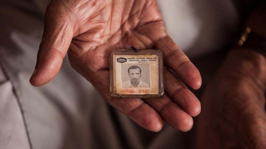 Mohammed Yaqub posa en su casa con su antigua tarjeta de Union Carbide, que lo acreditaba como trabajador de la fábrica. // FOTO: Bernat Parera