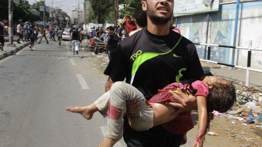 Un palestino traslada el cuerpo sin vida de un niño en Ráfah, tras el bombardeo israelí contra una escuela de la ONU para los refugiados palestinos / Hatem Ali \ AP Photo