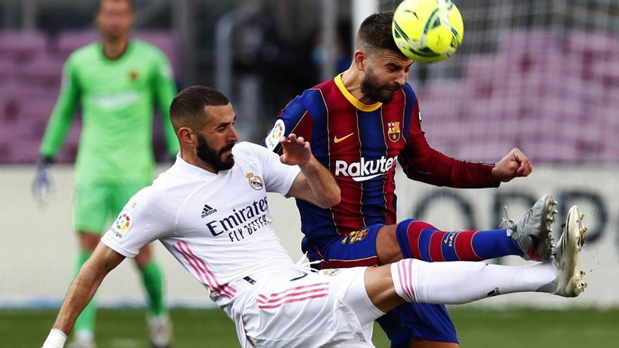 Karim Benzema y Gerard Piqué se disputan un balón