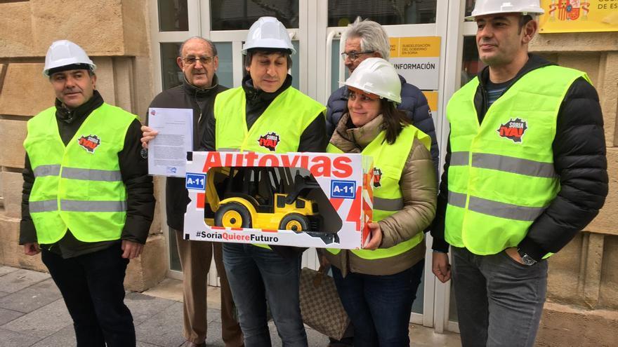 Miembros de Soria ¡YA! entregan la excavadora de juguete en la Subdelegación de Gobierno de Soria.