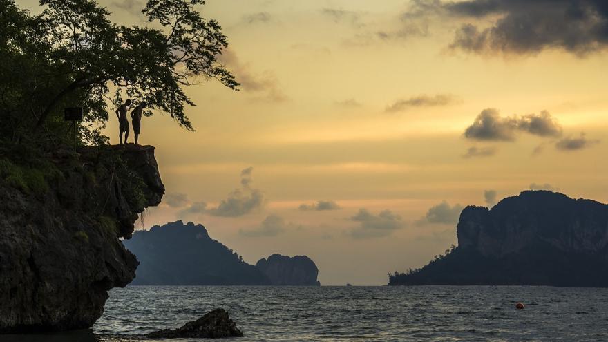 Dos turistas se piensan saltar en el extremo sur de la playa de Pranang, al atardecer. Al final no saltaron, como pedía el cartel. Foto: Guillén Pérez/ Flickr