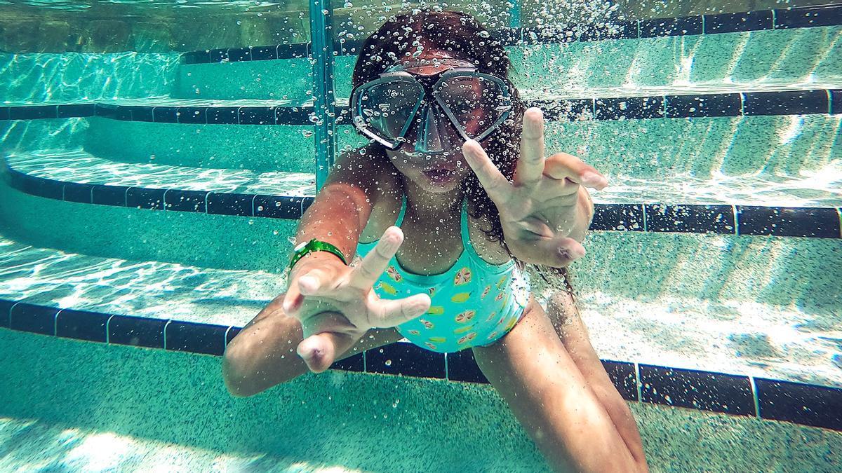 Una niña buceando en una piscina