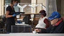 Una camarera atiende a varias personas sentadas en una terraza de Navarra donde los empleados utilizan un metro para asegurarse de que las medidas de distanciamiento son las correctas entre los potenciales clientes de la terraza de un bar en el centro de Pamplona, Navarra (España), durante el día 60 del estado de alarma, a 13 de mayo de 2020.