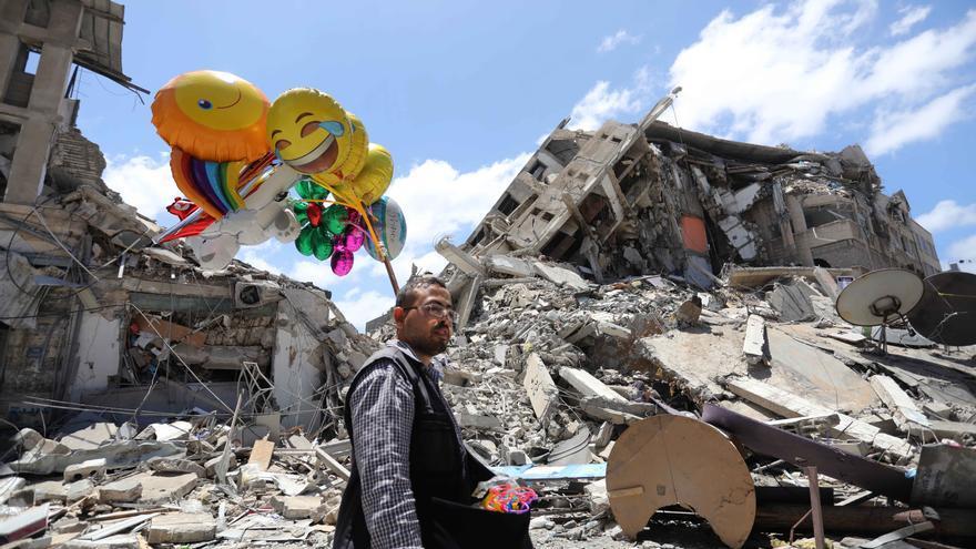 Un joven reparte globos y juguetes junto a las ruinas de los edificios que dejo la última ofensiva militar Israelí sobre Gaza.