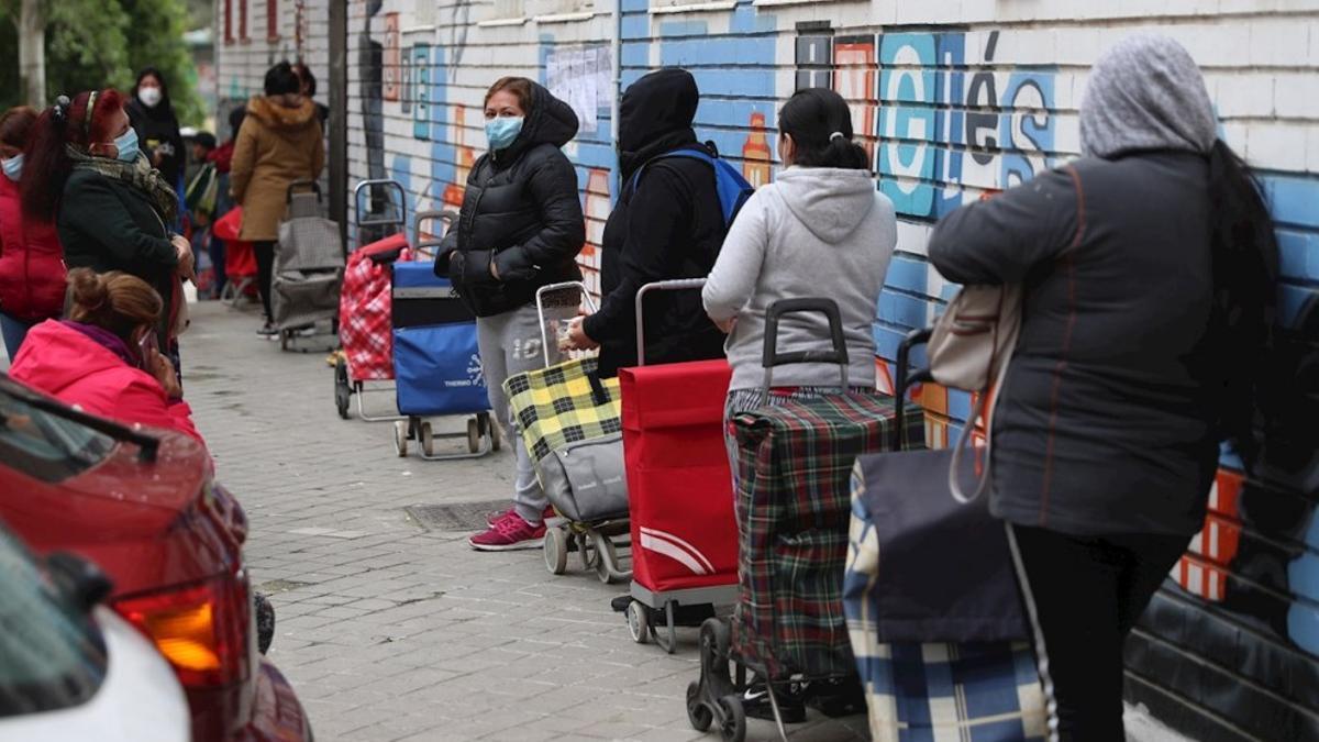 Varias personas hacen cola para recibir ayuda de un banco de alimentos.