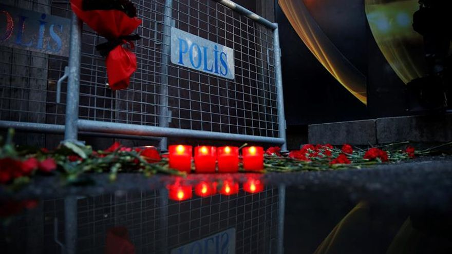 Ciudadanos colocan flores y velas en una barrera de la policía en frente de la discoteca Reina después del ataque cerca del río Bósforo, en Estambul