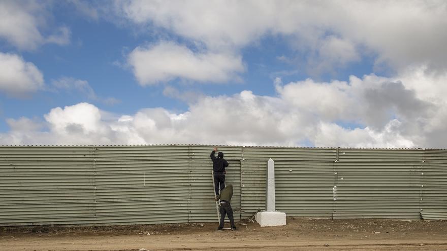 Soplete en mano, dos coyotes abren una puerta en la valla fronteriza de la colonia Libertad, en Tijuana.