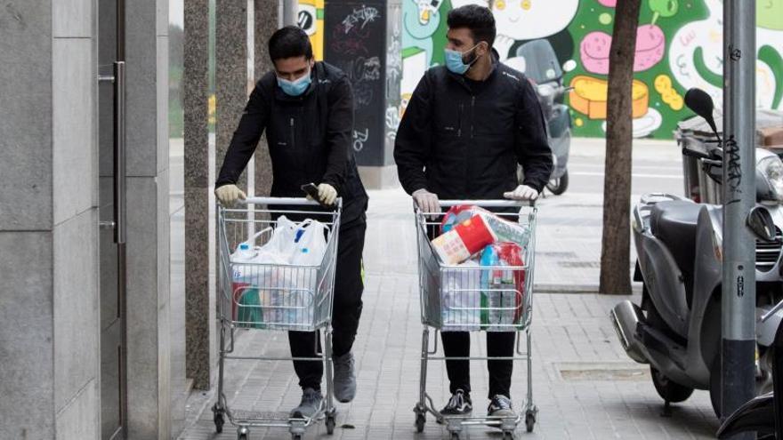 Dos trabajadores de un supermercado llevan una compra a un domicilio de Barcelona, este jueves.