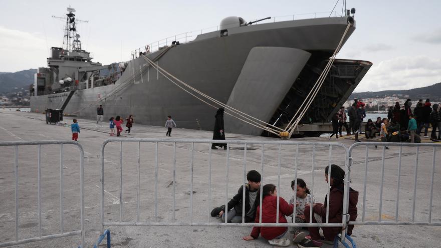 Migrantes que llegaron en días anteriores delante de un barco de la Armada griega que los transportará a tierra firme desde el puerto de Mytilene, en la isla de Lesbos, Grecia © REUTERS / Costas Baltas