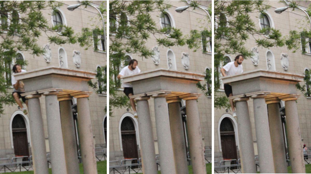 Uno de los jóvenes subiéndose a luna columna de la fuente de Recoletos | SOMOS CHUECA