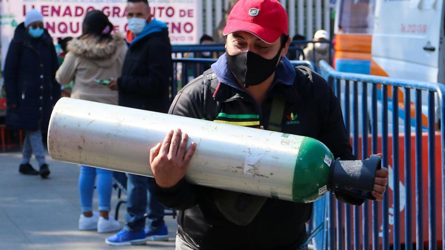 Una persona transporta un tanque de oxígeno mientras otras esperan turno para la carga de oxígeno en la alcaldía de Iztapalapa, en Ciudad de México.