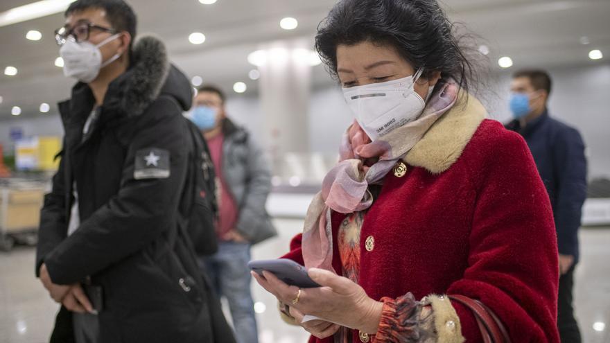 Una mujer consulta su teléfono en el aeropuerto de China durante los primeros días de contagio, en febrero.