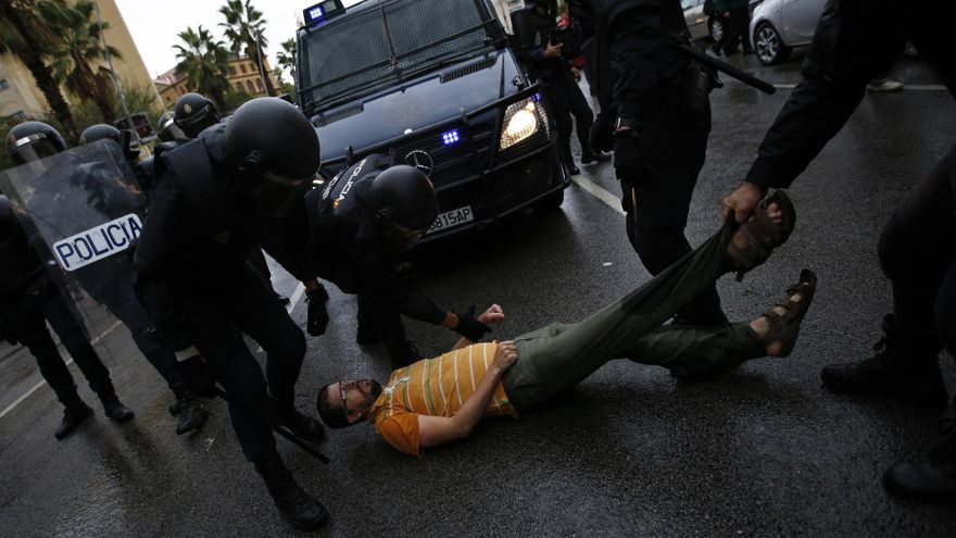 Descripción : Spanish National Police officers drags a man trying to block a police van outside the Ramon Llull school assigned to be a polling station by the Catalan government in Barcelona, Spain, early Sunday, 1 Oct. 2017. Catalan pro-referendum supporters vowed to ignore a police ultimatum to leave the schools they are occupying to use in a vote seeking independence from Spain.