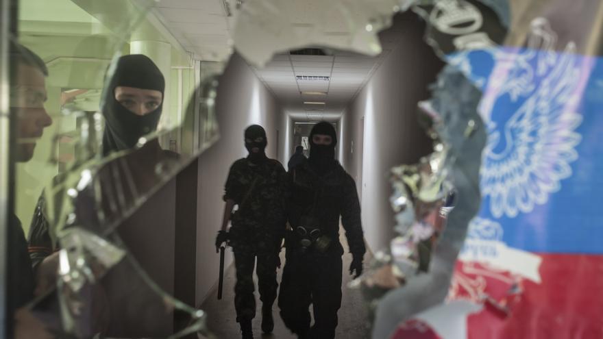 Militantes pro-rusos enmascarados patrullan en el edificio de la administración local en Mariupol, Ucrania, Sábado, 26 de abril 2014.Copy: AP Photo/Evgeniy Maloletka