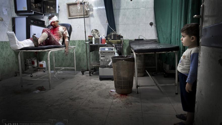 Un niño en el hospital Dar al-Shifa mire a los pacientes heridos. El hombre herido fue llevado junto a su esposa embarazada al hospital. Ambos están en estado crítico./ Niclas Hammarström