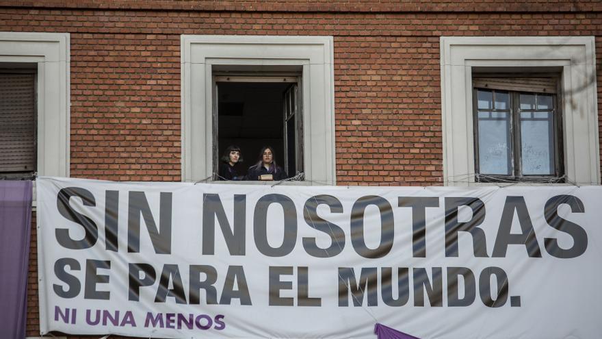 Un grupo de activistas feministas contemplan el arranque de la marcha de Madrid desde un balcón del centro social autogestionado la Ingobernable
