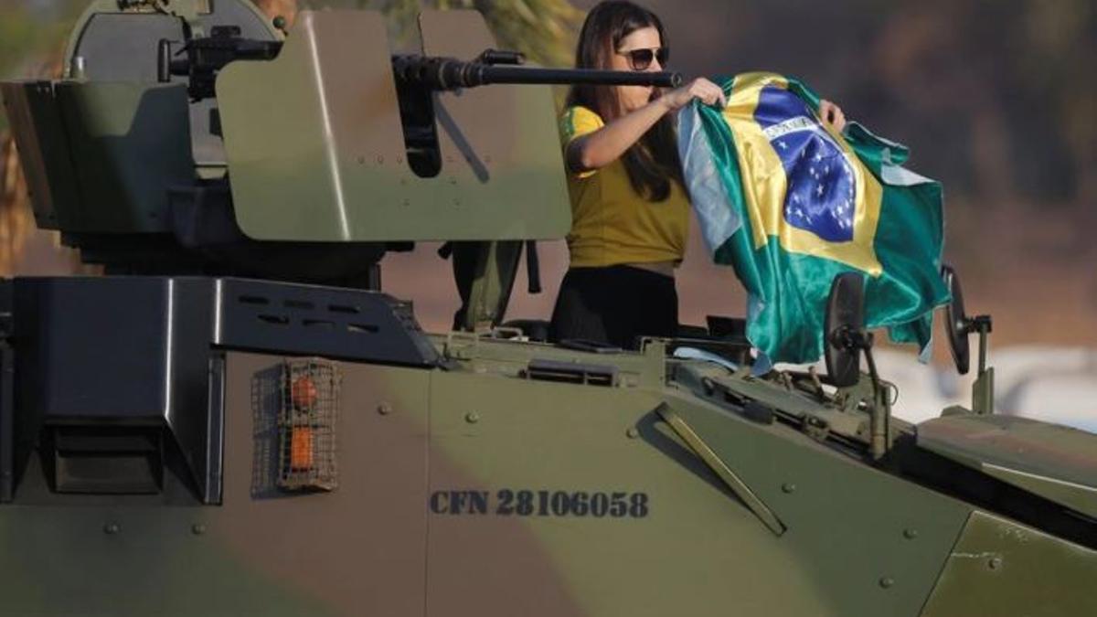 Una seguidora de Jair Bolsonaro exhibe una bandera brasileña montada en un tanque en Brasilia en el inicio de las manifestaciones a favor del ex militar