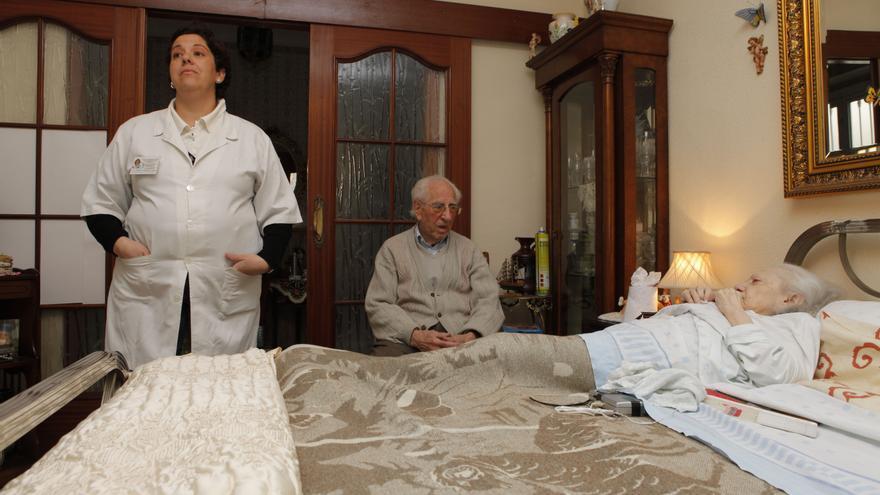 Dos usuarios del servicio de atención a la dependencia junto a su cuidadora, en Jaén.