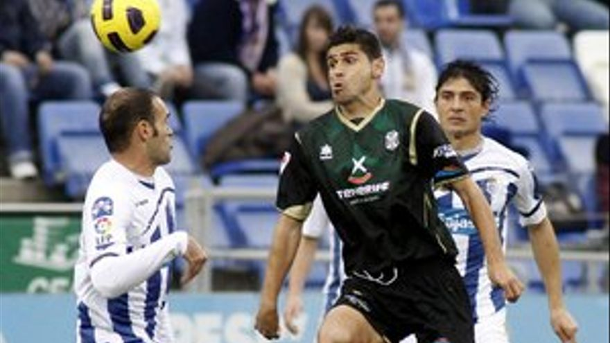 Antonio Hidalgo disputa un balón con dos jugadores del Recreativo.(ACFI PRESS)