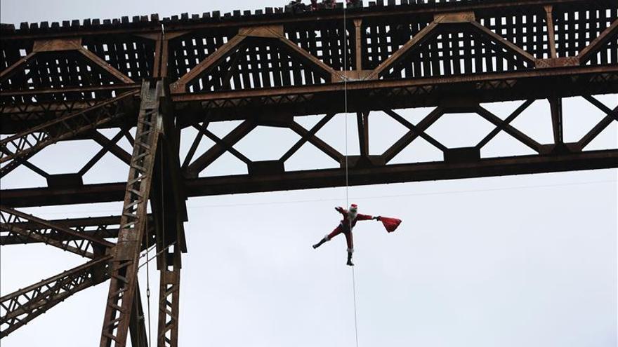 Un Papá Noel salta de un puente para dar regalos a los niños pobres de Guatemala