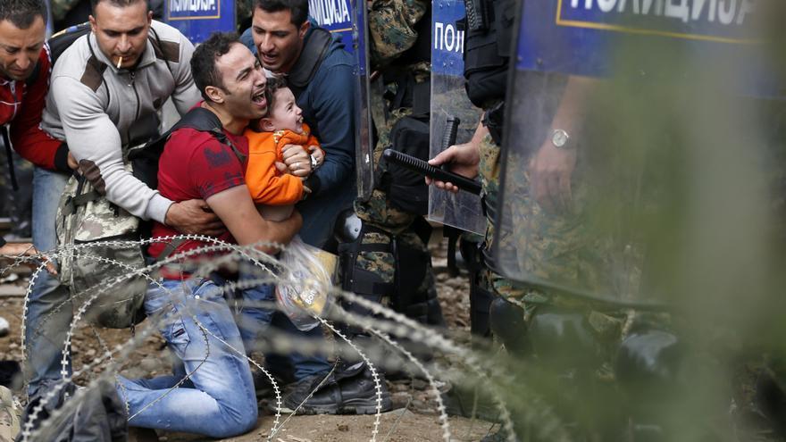 Dos hombres ayudan a un compañero que sostiene un niño ante la ante las fuerzas especiales macedonias mientras esperan el permiso policial para cruzar de Grecia a Macedonia. / Darko Vojinovic - AP