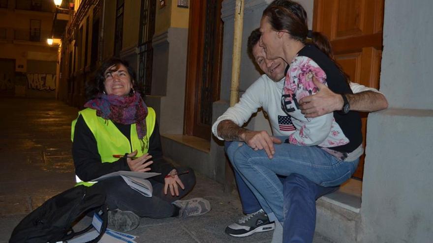 Una voluntaria entrevista a dos personas sin hogar en Valencia