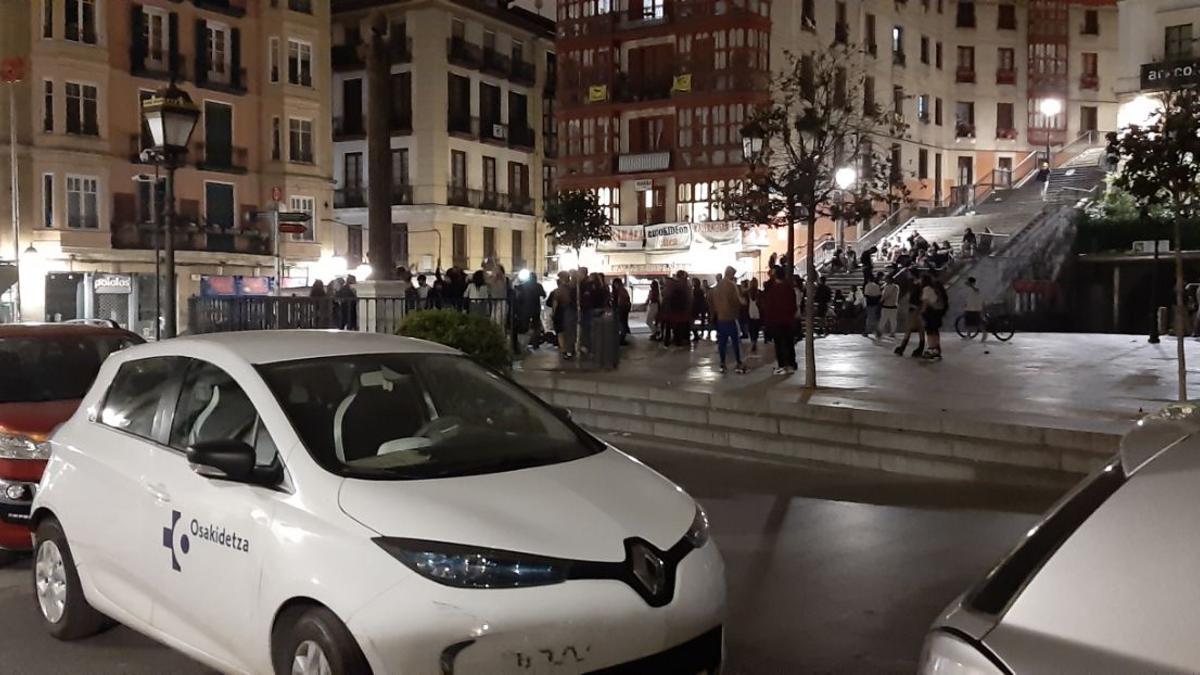 """Una treintena de jóvenes """"celebrando"""" el fin del estado de alarma en la plaza Unamuno de Bilbao junto a un coche de Osakidetza"""