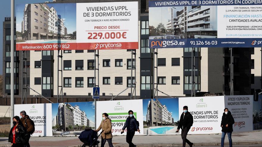 Varios viandantes pasan ante una promoción de viviendas en construcción en el barrio madrileño de El Cañaveral, en una fotografía de archivo. EFE/Chema Moya