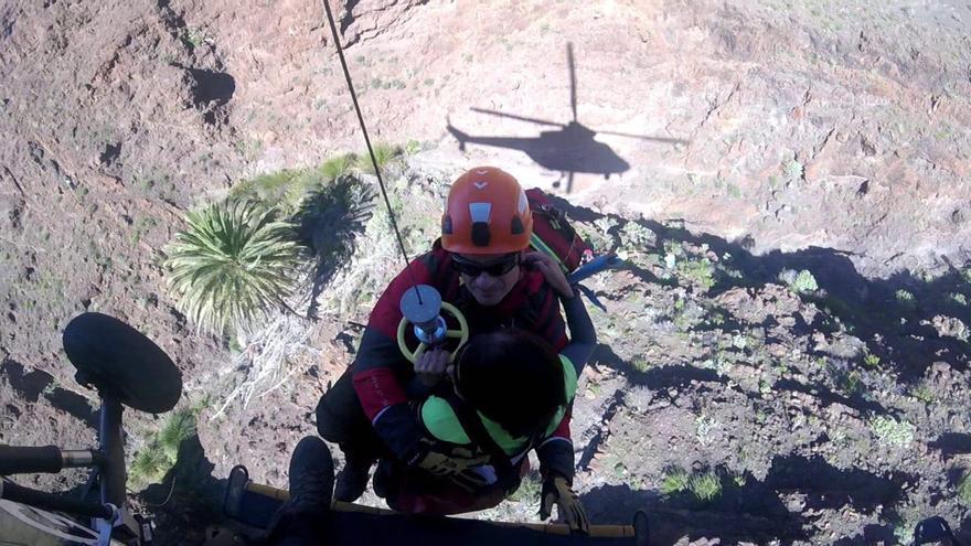 Uno de los integrantes del GES sube a la mujer accidentada hasta el helicóptero.