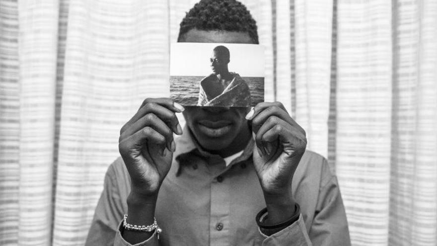 Malick posa para un retrato dentro de su habitación del Hotel Colibri, sosteniendo un retrato suyo