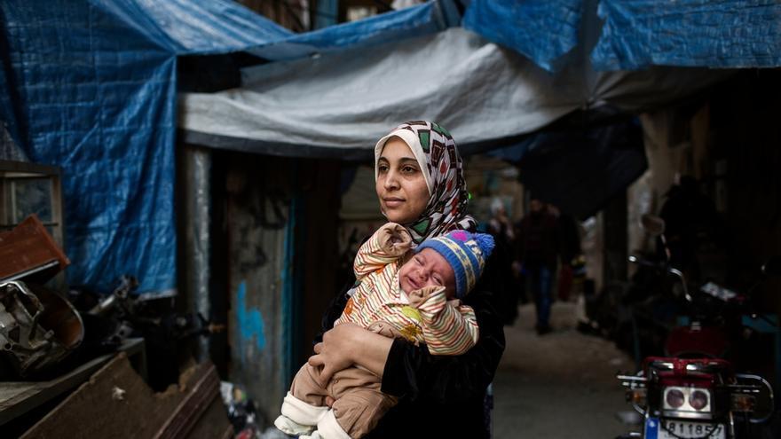 """Iman, madre de 4 hijos, sostiene a uno de sus bebés a las puertas de la unidad de maternidad de MSF en el campo de Shatila. Ha vivido refugiada en el Líbano durante los últimos tres años, después de haber huido de la guerra en Siria. Acude a la unidad de maternidad con regularidad para hacer un seguimiento de su bebé. """"No tenemos nada. Mi esposo no tiene trabajo estable y luchamos cada mes para poder sobrevivir"""". Fotografía: Diego Ibarra Sánchez"""