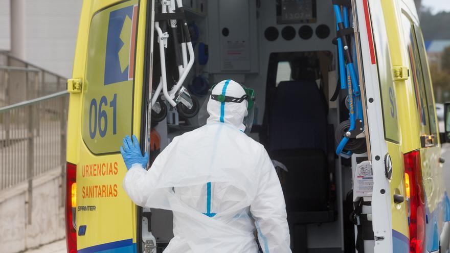 Un trabajador sanitario totalmente protegido cierra la puerta de una ambulancia