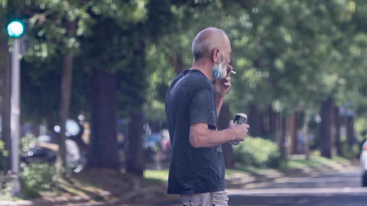 Un ciudadano fuma en la vía pública con su mascarilla en la barbilla, en una imagen de archivo.