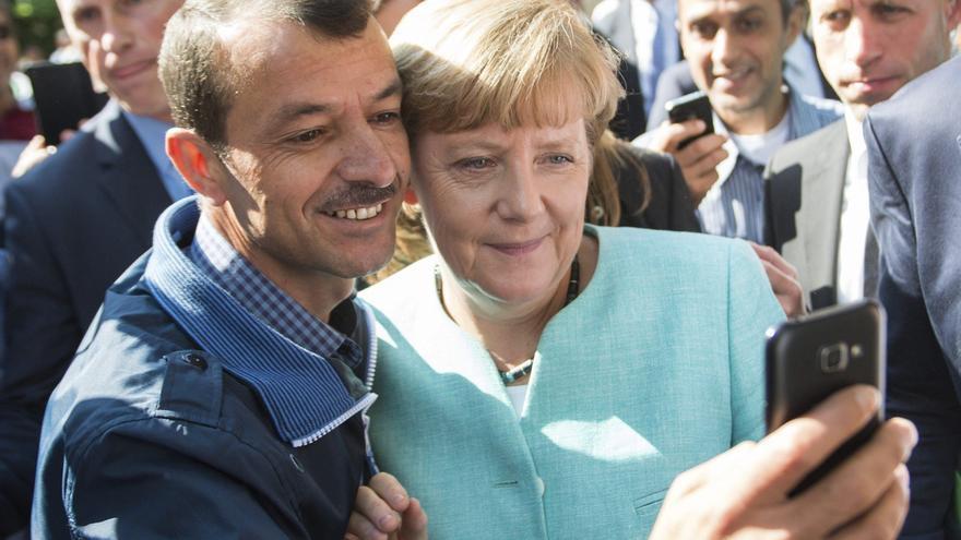 Un refugiado se toma una 'selfie' con Angela Merkel Angela Merkel durante la visita de la canciller a la Oficina Federal de Migración y Refugiados en Berlín.