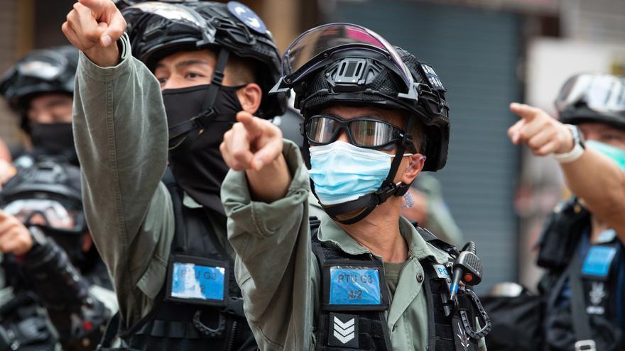 Varios policías señalan a manifestantes de una marcha prodemocrática en el 23 aniversario del establecimiento de la Región Administrativa Especial de Hong Kong.