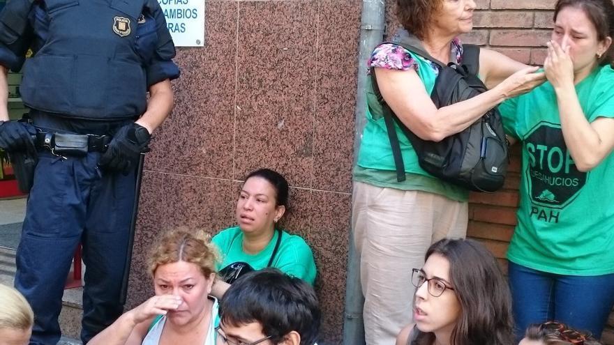 Activistas de la PAH delante de un mosso, en el momento del desahucio