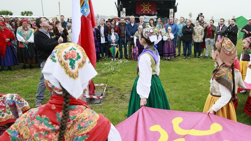 Niñas vestidas con el traje montañés y portando la bandera del lábaro cántabro.