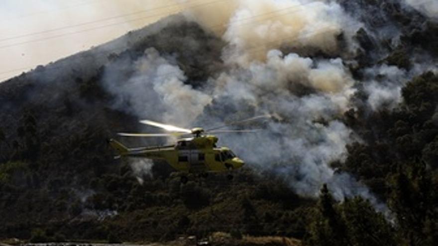 Helicóptero de extinción tras recoger agua en el río Sil, al fondo uno de los fo
