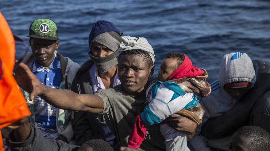 Las personas rescatadas cogen los chalecos salvavidas entregados por los socorristas de Open Arms.