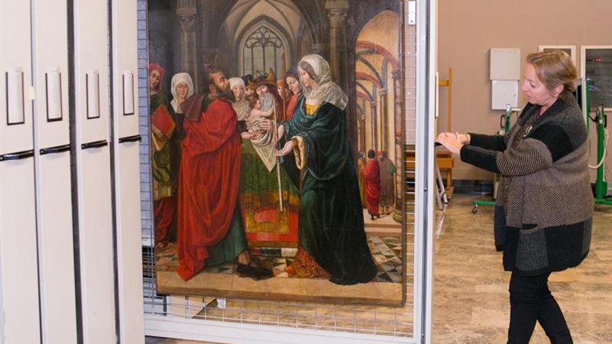 Una trabajadora del Museo de Zaragoza muestra la tabla que se ha recibido para su custodia procedente del retablo del altar mayor del Monasterio de Sijena hasta que se resuelva el litigio sobre la propiedad. EFE
