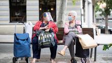 Dos mujeres con mascarillas sentadas en un banco