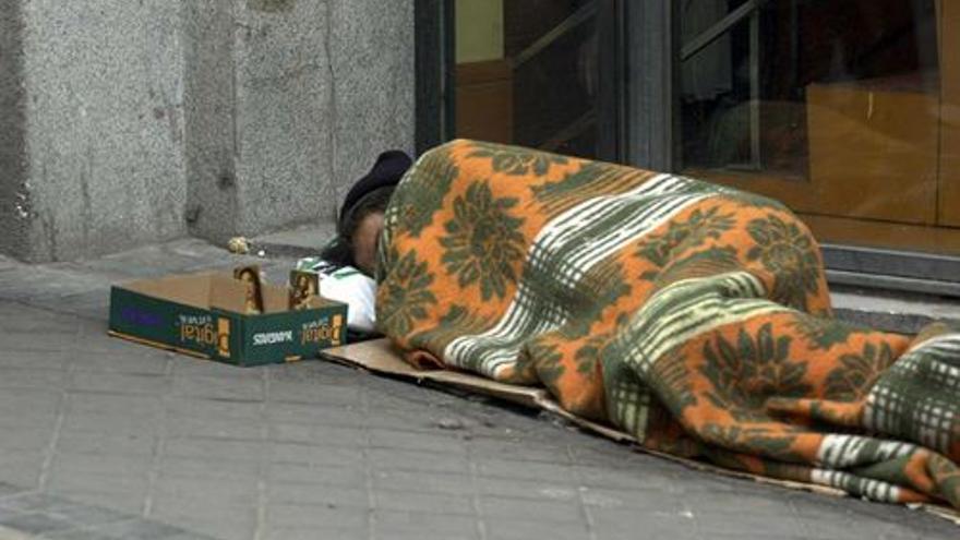 Una persona trata de evitar el frío mientras duerme en plena calle. / Europa Press