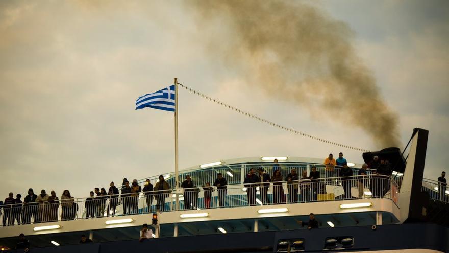 Justo debajo de la bandera griega, Mashid, Abdallah y Rashad (de izquierda a derecha) esperan que el barco atraque en el puerto del Pireo / FOTO: Aitor Sáez