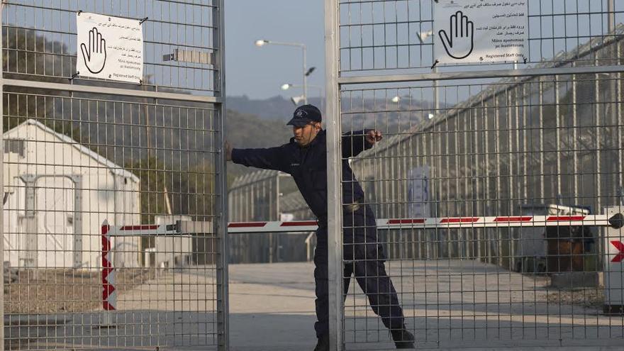 Un policía griego cierra la puerta de entrada del campo de Moria, que hasta este lunes era un albergue para migrantes y refugiados. Sólo en Grecia sobrepasan ya los 50,000 y las llegadas diarias no parecen decrecer.   AP Photo/Petros Giannakouris