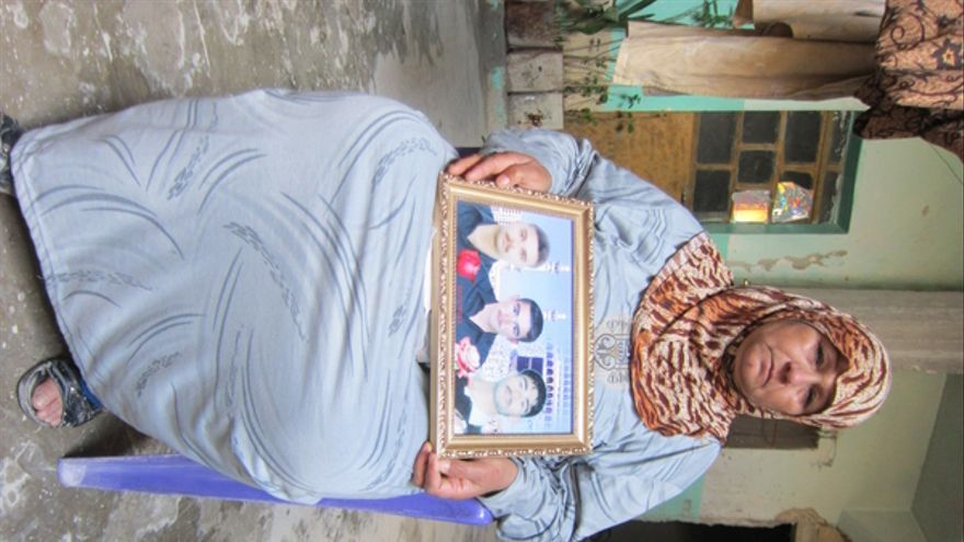 """La madre de tres jóvenes asesinados en Samin (Siria) muestra la foto de sus tres hijos. La mujer dijo a Amnistía Internacional: """"Ellos mataron a mis hijos, lo que más quería en el mundo, y, además, profanaron sus cadáveres prendiéndoles fuego. ¿Cómo puede una madre aguntar este dolor?"""" © Amnistía Internacional"""