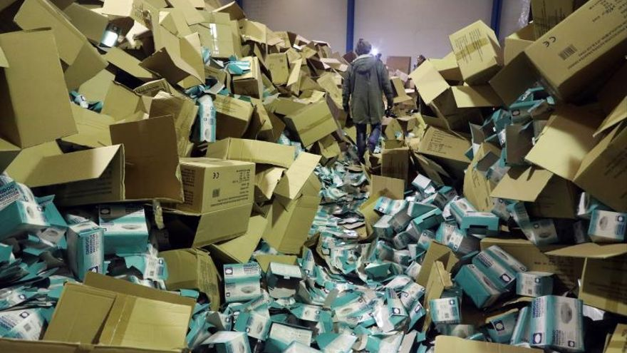 Un fotógrafo camina entre las cajas de material sanitario almacenado en el interior de una nave del polígono del Tambre en Santiago de Compostela, durante la redada policial de ayer para descubrir el robo de cerca de dos millones de mascarillas y otro material sanitario, valorado en cinco millones de euros.
