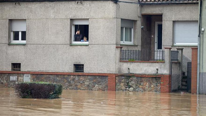 Unos vecinos observan desde su casa el río Ter, que se ha desbordado a su paso por la ciudad de Girona, en el punto más bajo de su recorrido, junto a la carretera C-255, más allá del puente del Agua este miércoles.