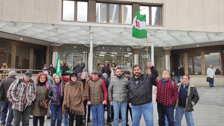 El líder del SAT, Óscar Reina, con el puño en alto, junto a varias personas que le han acompañado este 12 de diciembre al juicio en Madrid.